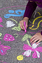 Germany, Girl drawing on street with chalk - SARF000047
