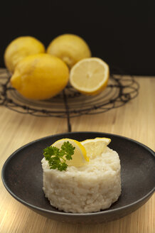 Lemon risotto with lemon on wooden table, close up - OD000193