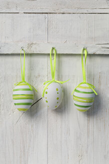 Easter eggs hanging on wooden door, close up - ASF005033