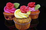 Cup cake with buttercream topping on black background, close up - HOHF000176