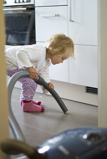 Germany, Kiel, Girl cleaning kitchen with hoover - JFE000161