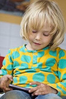 Germany, Kiel, Girl playing with smartphone, smiling - JFE000158