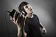 Germany, Cologne, Young man with headphones listening music from smart phone - JAT000111
