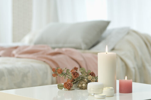 Candles, skin cream and bunch of roses on table with bed in background - ASF005038