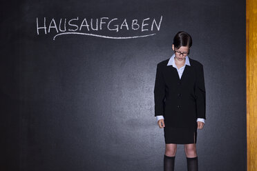 Girl standing in front of blackboard - MAEF006913
