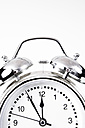 Alarm clock showing time against white background, close up - SKF001414