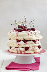 Pavlova with whipped cream, cherries, cherry sauce and icing sugar on cake stand, close up - EC000258