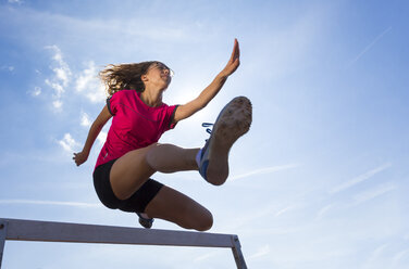 Germany, Young woman athlete jumping hurdles on track - STSF000076