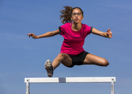 Germany, Young woman athlete jumping hurdles on track - STSF000062