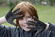 France, Boy showing dirty black hands, Smiling, close up - LBF000160