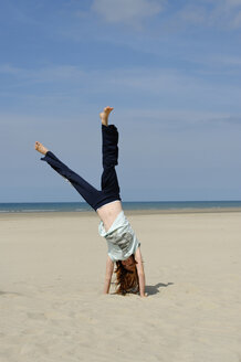France, Girl doing handstand at beach - LB000163
