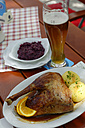 Germany, Bavaria, Plate of meat with beer glass on wooden table, close up - LB000149