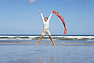 New Zealand, Mature woman jumping at Ninety Mile Beach - GW002314