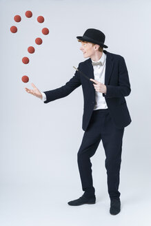 Young man showing magic with ball, smiling - TCF003486