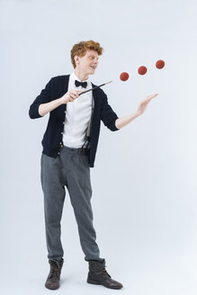 Young man showing magic with ball, smiling - TCF003496