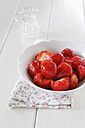 Bowl of strawberries on wooden table, close up - EVGF000151