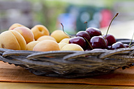 Germany, Bavaria, Landshut, Bowl of cherries and apricots on wooden table, close up - SAR000062
