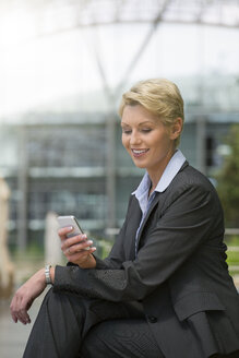 Germany, Hannover, Businesswoman using smart phone, smiling - KFF000196