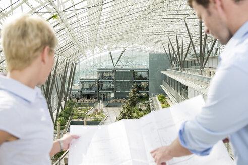 Germany, Hannover, Business people holding blueprint - KFF000115