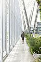Businesswoman walking in modern courtyard - KFF000160