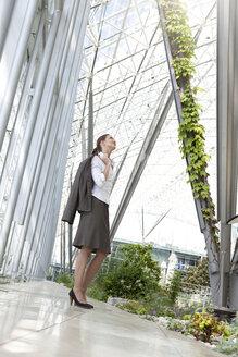 Businesswoman standing in modern courtyard - KFF000162