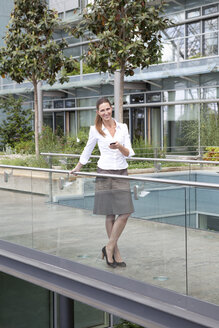 Businesswoman with cell phone on footbridge - KFF000145