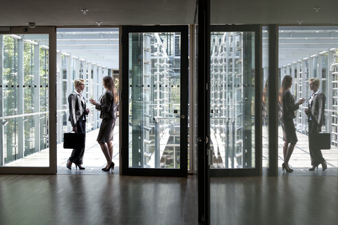 Two businesswomen talking in office building - KFF000168