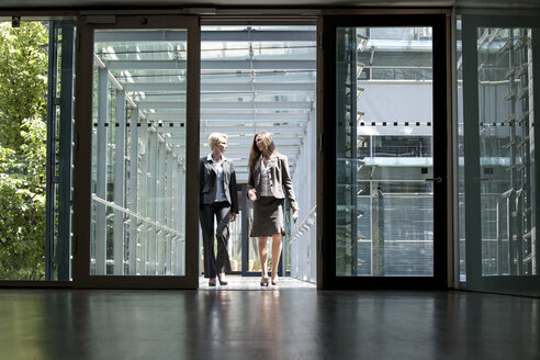 Two businesswomen talking in office building - KFF000128