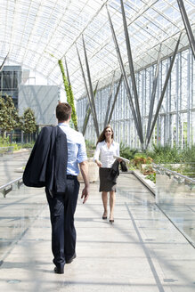 Businessman and businesswoman walking at modern office building - KFF000135