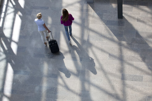 Woman walking with rolling suitcase accompanied by friend - KFF000149