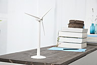 Germany, North Rhine Westphalia, Modern windmill and stack of books on table - PDF000336