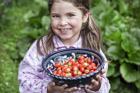 Germany, North Rhine Westphalia, Cologne, Portrait of girl holding bowl of strawberries, smiling - FMKYF000501