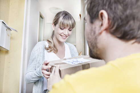 Germany, North Rhine Westphalia, Cologne, Young woman taking pizza box from delivery man, smiling - FMKYF000483