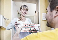 Germany, North Rhine Westphalia, Cologne, Young woman taking pizza boxes from delivery man, smiling - FMKYF000480