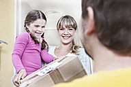 Germany, North Rhine Westphalia, Cologne, Mother and daughter taking letters from postman, smiling - FMKYF000508