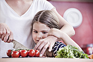 Germany, North Rhine Westphalia, Cologne, Mother and daughter cutting vegetables - FMKYF000472
