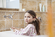 Germany, North Rhine Westphalia, Cologne, Portrait of girl brushing teeth in bathroom - FMKYF000469
