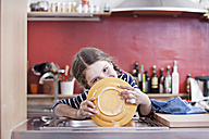 Germany, North Rhine Westphalia, Cologne, Girl washing plates in kitchen sink, close up - FMKYF000457