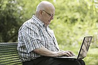 Germany, North Rhine Westphalia, Cologne, Senior man using laptop on bench in park - JAT000154