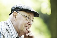Germany, North Rhine Westphalia, Cologne, Senior man with cap and glasses in park, close up - JAT000122