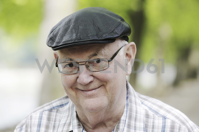 Germany, North Rhine Westphalia, Cologne, Portrait of senior man with cap and glasses in park, smiling - JAT000126