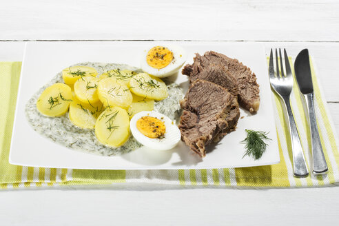Beef with dill sauce, potatoes and boiled egg on plate, close up - MAEF007083