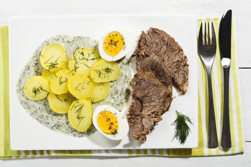 Beef with dill sauce, potatoes and boiled egg on plate, close up - MAEF007084