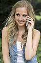 Germany, Oberhausen, Young woman talking on mobile phone, smiling - GDF000140