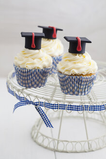 Graduation cupcakes with vanila frosting on cake stand, close up - ECF000281