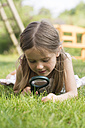Germany, Bavaria, Girl looking through magnifying glass in graden - SARF000075