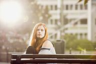 Germany, Berlin, Portrait of woman sitting on bench - ZMF000014