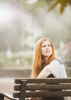 Germany, Berlin,Young woman sitting on bench and looking away - ZMF000012