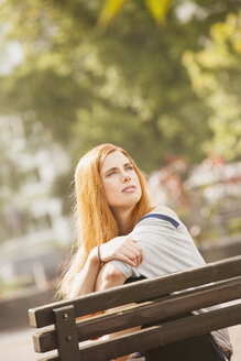 Germany, Berlin,Young woman sitting on bench and looking away - ZMF000011