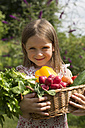 Germany, Bavaria, Portrait of girl holding basket full of vegetables, smiling - SARF000074